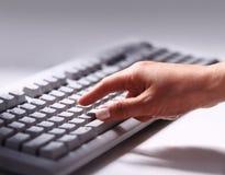 键入在键盘的女性办公室工作者 免版税库存图片