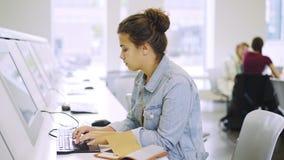 键入在键盘的年轻女人在显示器和笔记薄附近 股票录像