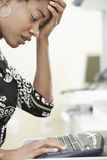 键入在键盘的担心的女实业家 免版税库存照片