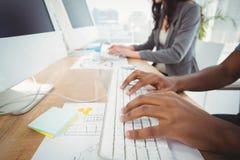 键入在键盘的播种的手在有工友的计算机书桌 免版税库存照片