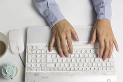 键入在键盘,白色计算机的女性手 免版税库存照片