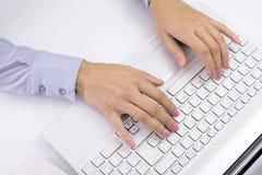 键入在键盘,白色计算机的女性手 免版税库存图片