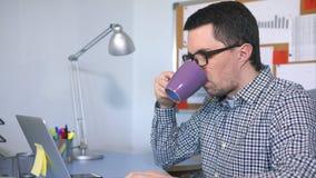 键入在键盘,看屏幕和喝咖啡的男性计算机用户 股票视频