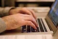 键入在他的膝上型计算机的人 免版税库存照片