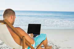 键入在他的膝上型计算机的英俊的人,当坐他的甲板柴时 库存照片