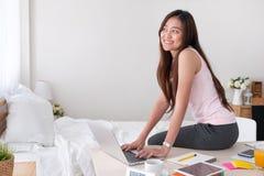 键入在tabl的膝上型计算机的亚洲女性自由职业者穿戴背心衬衣 库存图片