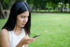 键入手机的女孩 免版税库存照片