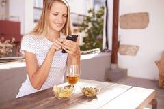键入消息的微笑的白肤金发的女孩 免版税库存图片