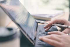 键入电子片剂键盘船坞驻地的男性手特写镜头视图  使用流动触感衰减器的博客作者为工作 免版税库存图片