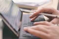 键入电子片剂键盘船坞驻地的男性手特写镜头视图  使用流动触感衰减器的博客作者为工作 免版税库存照片