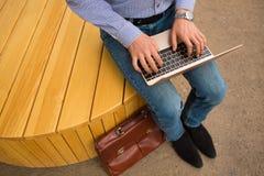 键入的人特写镜头  办公室工作者与一台新的膝上型计算机坐都市背景 进步技术概念 免版税库存图片