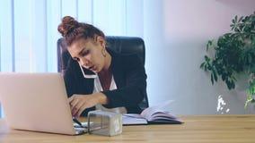 键入的女孩在时髦的衣裳打扮,当在办公室坐膝上型计算机时 影视素材