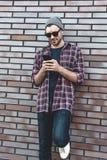 键入的正文消息 英俊的年轻人侧视图拿着手机的聪明的便衣的,当倾斜在砖墙时 库存图片