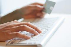 键入键盘和拿着网上购物的一张信用卡 免版税图库摄影