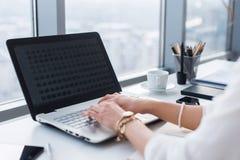 键入,使用个人计算机的女性手的侧视图图片在一个轻的办公室 工作在工作场所的设计师,搜寻新的想法 库存照片
