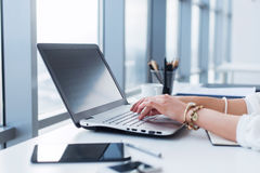 键入,使用个人计算机的女性手的侧视图图片在一个轻的办公室 工作在工作场所的设计师,搜寻新的想法 免版税库存照片