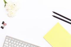 键盘、一个黄色垫、两黑铅笔、菊花花和夹子纸的在白色背景 平的位置 免版税库存照片