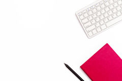 键盘、桃红色日志和一支黑笔在白色背景 最小的女性企业概念 平的位置 免版税库存照片