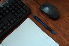 键盘、老鼠、笔记本和笔在桌上 库存图片