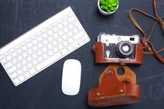 键盘、老鼠和照相机在一张黑桌上说谎 免版税图库摄影