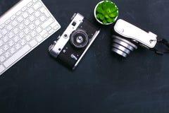 键盘、老鼠和照相机在一张黑桌上说谎 免版税库存照片
