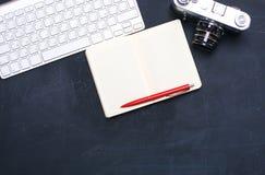 键盘、老鼠和照相机在一张黑桌上说谎 库存照片