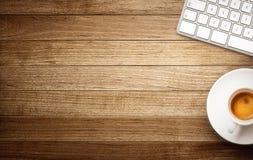 键盘和咖啡杯在木背景 图库摄影