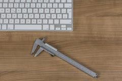键盘和游标卡尺在桌面上 库存照片