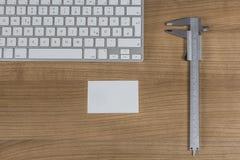 键盘和游标卡尺在桌面上 库存图片