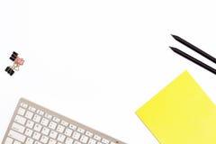 键盘,一个黄色垫,纸的两黑铅笔和夹子在白色背景 工作pla的最小的企业概念 库存图片