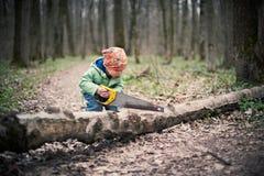 锯一棵下落的树的小男孩在森林里 免版税库存图片