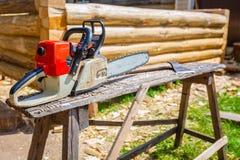 锯和木头砍刀或者轴为修建从木材杉木和裂片的木屋使用在地面上 库存图片