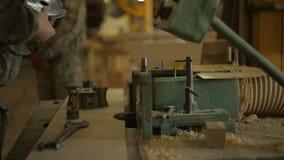 锯木厂的工作者更换在渐近的机器的切削刀并且设定木材加工的机器,特写镜头 影视素材