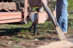 锯木厂碾碎的木材的工作者 免版税库存图片