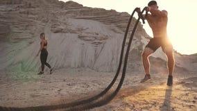 锻炼的运动人在日落的沙子小山附近击中在地面上的绳索并且培养了尘土 股票视频