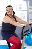 锻炼脚踏车的肥胖妇女 免版税库存照片