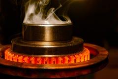 锻烧在工厂感应炉的特写镜头高热金属钢齿轮零件有烟的 免版税库存照片