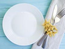 镀叉子刀子黄色花庆祝春天言情蓝色木背景 库存图片