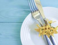 镀叉子刀子黄色花庆祝言情蓝色木背景 库存照片