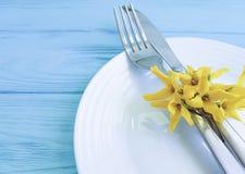 镀叉子刀子黄色花言情蓝色木背景 免版税库存照片