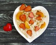 镀心脏燕麦粥粥,草莓,在木背景的杏子 图库摄影