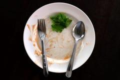 镀绿色菜空的垃圾食物和叶子在米、板材叉子和匙子板材的  免版税库存图片