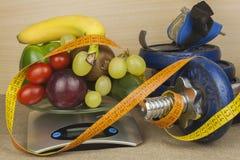 镀铬哑铃围拢用健康水果和蔬菜在桌上 健康吃和减重的概念 免版税库存照片