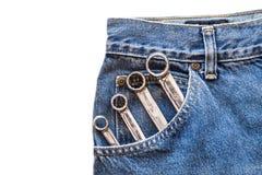 镀铬在前面蓝色牛仔裤的把手扳手装在口袋里在白色被隔绝的背景 图库摄影