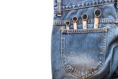 镀铬在后面蓝色牛仔裤的把手扳手装在口袋里在白色被隔绝的背景 免版税库存图片