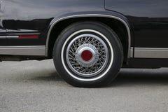 镀铬有银色轮幅和新的橡胶的轮子在黑发光的卡迪拉克 免版税库存图片