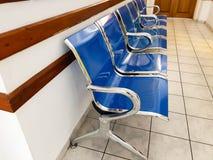 镀铬物和蓝色空的塑料位子在医院走廊 免版税库存图片