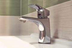 镀铬物龙头水盆 在卫生间里关闭了轻拍水滴水 浪费水 抬头与白色水槽的银色颜色在 库存照片