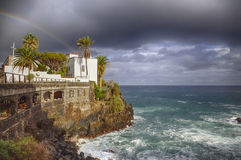 镇在岩石和海的市政厅挥动在彩虹下 免版税库存照片