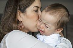 镇定一个哭泣的婴孩的年轻母亲 库存图片